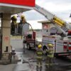Firefighters use power equipment to cut into the pillar at the Petro Canada gas station